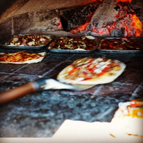 Cooking some tasty pizza in Clyde Park's woodfire oven!