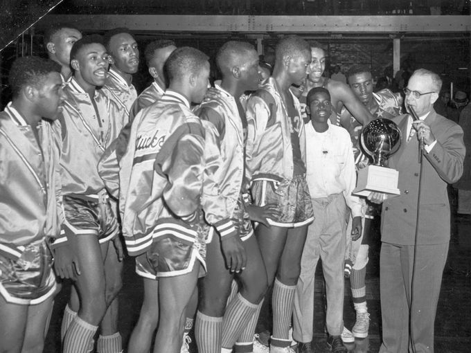 The Crispus Attucks High School basketball team took the Indiana High School Championship trophy in 1955.