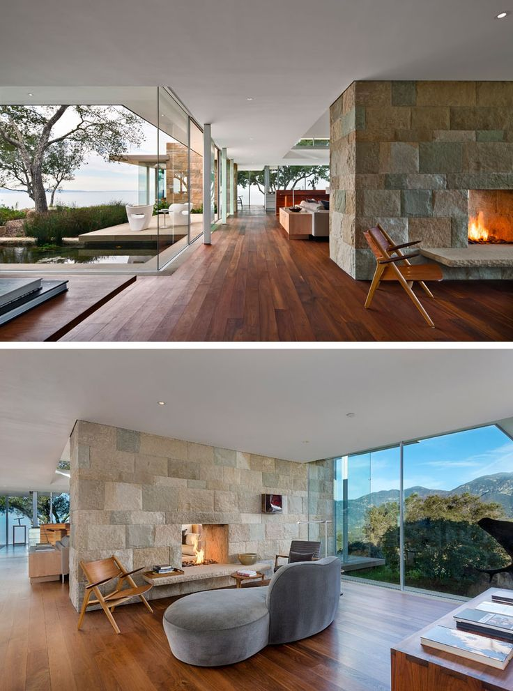 This modern house is spacious with walnut floors and plenty of glass. In the main living area, there's a double-sided fireplace with a stone surround. On one side of the fireplace is the den, and on the other is the living room and kitchen.