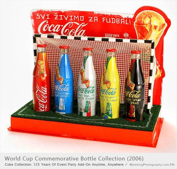 *COCA-COLA ~ five bottle set with display box wrapped with country flag ~ Germany, Brazil, Italy, Argentina and one bottle with large tropy image. Bottles sit in the slots in base of box with artificial green grass with goal lines, a net is affixed to box behind bottles, behind the net is a board with Cocca-Cola logo and World Cup trophy for 2006 FIFA World Cup Germany.