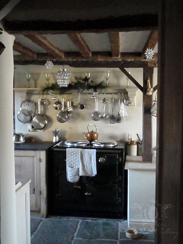 really like the mantel shelf with the rod to hang pots & pans above the stove, stone floor & beams ~ also like the long quilted oven mitt hanging from the stove handle ~ from The Paper Mulberry