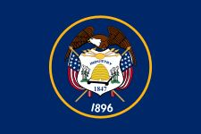The flag of the state of Utah was adopted in 1913 and consists of the seal of Utah encircled in a golden circle on a background of dark navy blue.