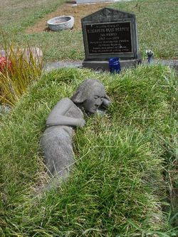 woman figure lying in grass - Located at Swanson Cemetery in New Zealand
