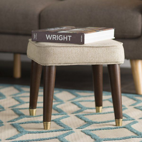 Gleaming golden leg caps highlight this chic stool, while linen-hued upholstery gives it a touch of comfort. Set it in the den to kick your feet up during movie night, or add it to the guest room to stage a stack of plush folded towels.