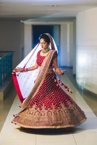 Twirling Brides - Bride in a Red and Gold Lehenga with a Net Dupatta | WedMeGood Photo by: Shaadi Moments #wedmegood #indianbride #indianwedding #red #bridal #pink #weddinglehenga #redbridallehenga
