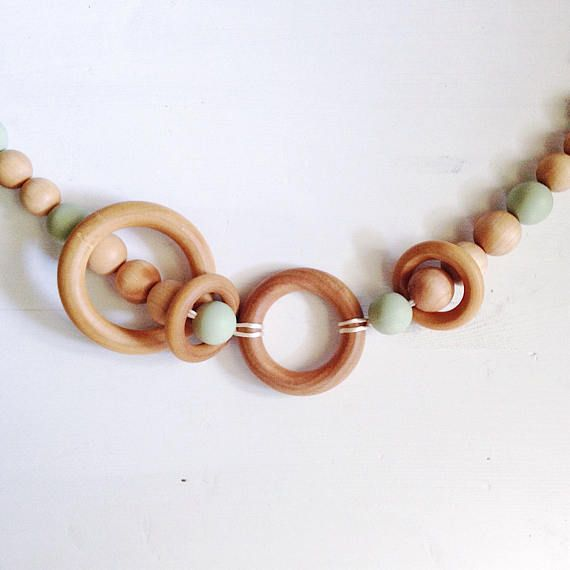 Our eco-friendly wooden pram garlands are the perfect sensory toy for your teething babes and growing toddlers. They will enjoy spinning the natural wood rings and hearing them rattle against the wooden & silicone beads. And since teething babies love putting everything in their mouth you will have peace of mind that our natural materials are free of any toxins. Attach this garland to your pram, moses basket, or play-yard for stationary play; or you can attach it to your car seat or stro...