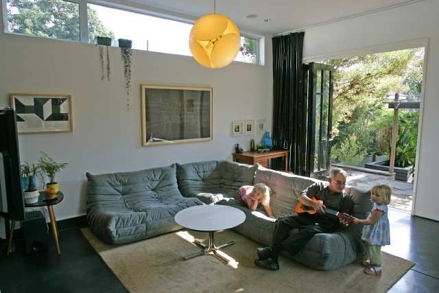 Rei and Marni Thompson play with Grandpa Ross Rudolph on Togo in their Atwater living room. Credit: Los Angeles Times @lignerosetwe