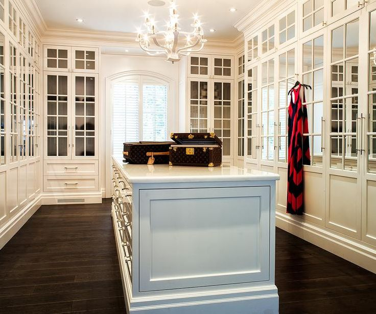 Chic Walk In Closet Features A Large Closet Island Fitted With Jewelry  Drawers Topped With Louis