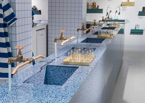 Project Ocean exhibition and Water Bar at Selfridges. The bar is made from a terrazzo material comprising recycled glass and epoxy resin, with taps and pipes in copper and brass. A seating area is formed with enamelled metal and brass tables, paired with wood and terrazzo stools.