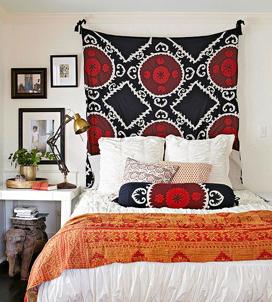Tapestry Headboard - Hang fabric behind your bed for a headboard that packs a patterned punch. Almost any fabric will do -- think vintage quilts or tapestries, drapes, or even a pretty flat sheet.