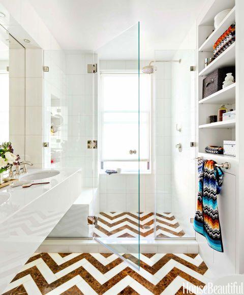 Azulejos Glassos en Vetro Bianco en las paredes y la vanidad reflejan la luz maravillosamente.  El galón en el suelo, compuesto por Dark Emperador y mármol de Tasos, fue cortada a medida por Manhattan renovaciones.  Sistema de ducha Yota y Tara toallero de Dornbracht.