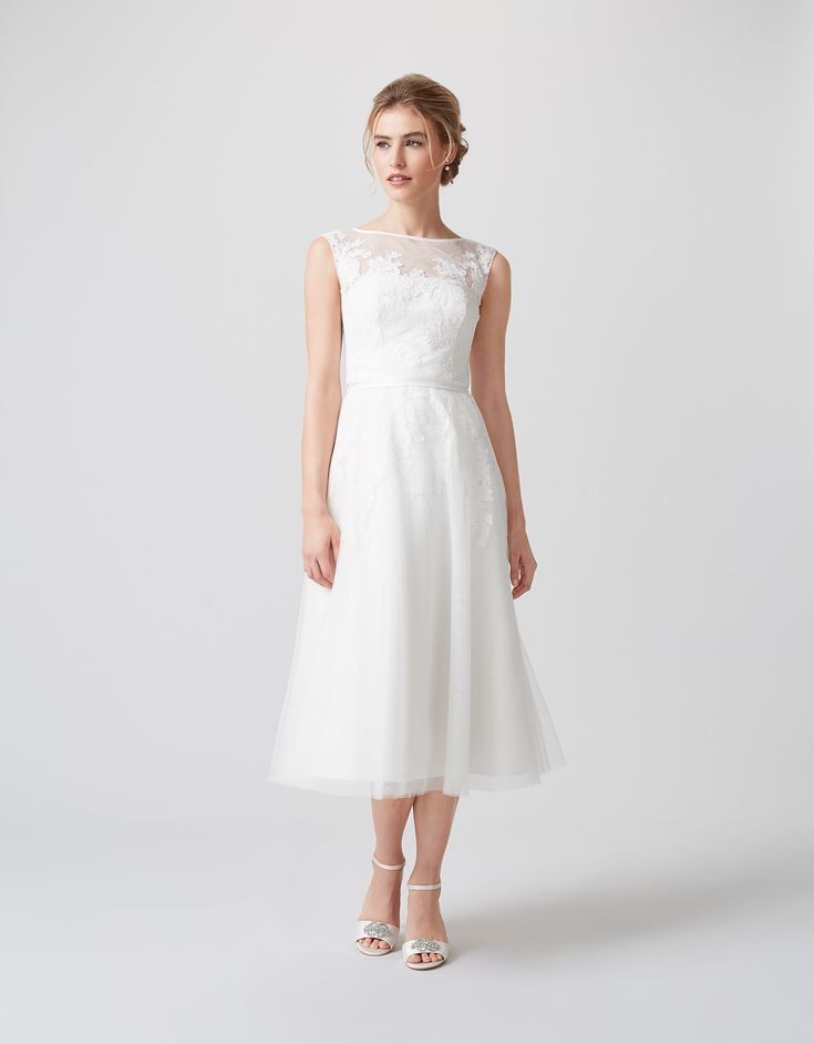 With a feminine, fifties-inspired midi length, our Verity ivory wedding dress is layered with heavenly tulle and lace for a dreamy finish. Sheer across the s...