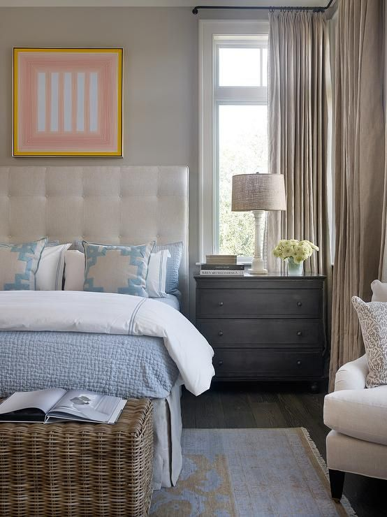 Transitional bedroom features pale gray painted walls lined with an ivory tufted headboard on bed dressed in white and blue bedding as well as blue Greek key pillows and a linen pleated bedskirt atop a blue and gold rug next to a dark stained 3 drawer nightstand and an alabaster lamp placed under window dressed in beige linen curtains.