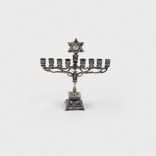 Delicată menora miniaturală, din argint, decorată cu steaua lui David, sfârșitul sec. XIX Atelier Olandez argint 833 turnat, cizelat, h=9 cm, 40 g Preţ de pornire: € 60 Baza piesei este sub forma unui trunchi de piramidă din care se prelungește o tijă centrală, suport pentru brațele luminilor realizate în chip de ramuri stilizate. Steaua lui David marchează centrul ansamblului.