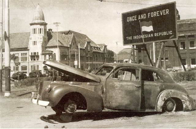 Several days ago on November 10th 1945, the wrecked car of AWS Mallaby at Surabaya, in front of Internatio building, behind the republican banner.  (Source: imperial war museum)