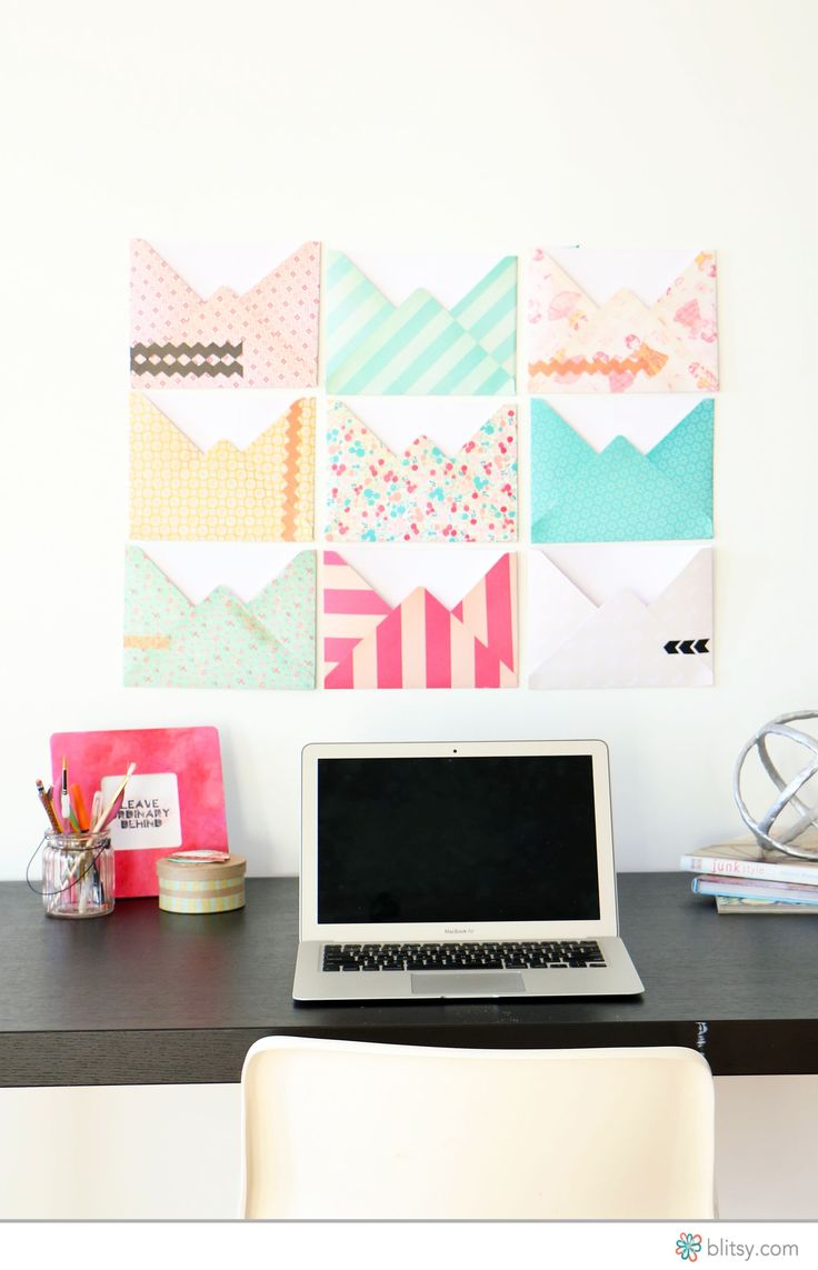 Colorful and patterned paper transformed into giant envelopes to hang on the wall and organize your office area.