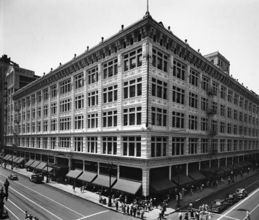 """A high-angle view of the May Company Building with people walking along the sidewalk on the corner of Eighth Street and Broadway :: """"Dick"""" Whittington Photography Collection, 1924-1987"""