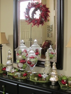 Entry table / buffet Christmas accessorizing. Love the apothecary jars filled with ornaments.