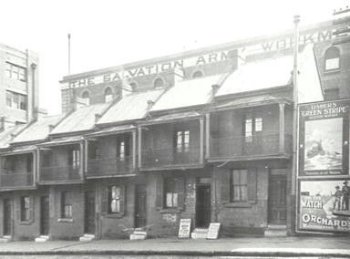 42-52 Liverpool St,Sydney from SussexStto Harbour Place. Row of terrace houses with Salvation Army Workmen's Metropole behind. •City of Sydney Archives•