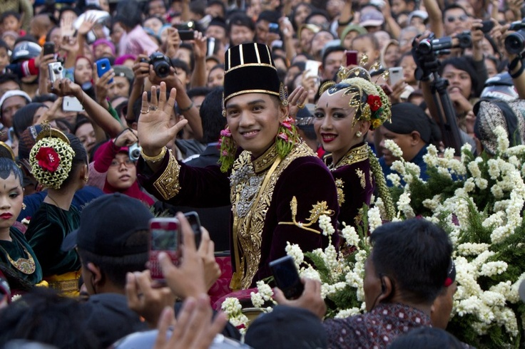 Kanjeng Pangeran Haryo Yudanegara (L) and his wife Gusti Kanjeng Ratu Bendara wave to people as they were driven in a horse-drawn carriage on the street of the ancient city of Yogyakarta, Indonesia. Yudanegara married Bendara, the youngest daughter of Sultan Hamengkubuwono X after three days of continuous ceremonies
