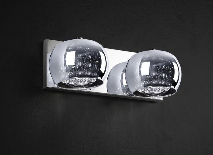 Ekskluzywny, podwójny kinkiet z kolekcji Zuma Line Crystal wykonany z chromowanego metalowego korpusu i szklanego kloszu dodatkowo ozdobionego kryształkami, jest unikatowym i nowoczesnym rozwiązaniem oświetlenia salonu, jadalni, kuchni, czy też sypialni oraz przedpokoju, zarówno w eleganckim w stylu glamour jak i w minimalistycznym, skandynawskim klimacie.
