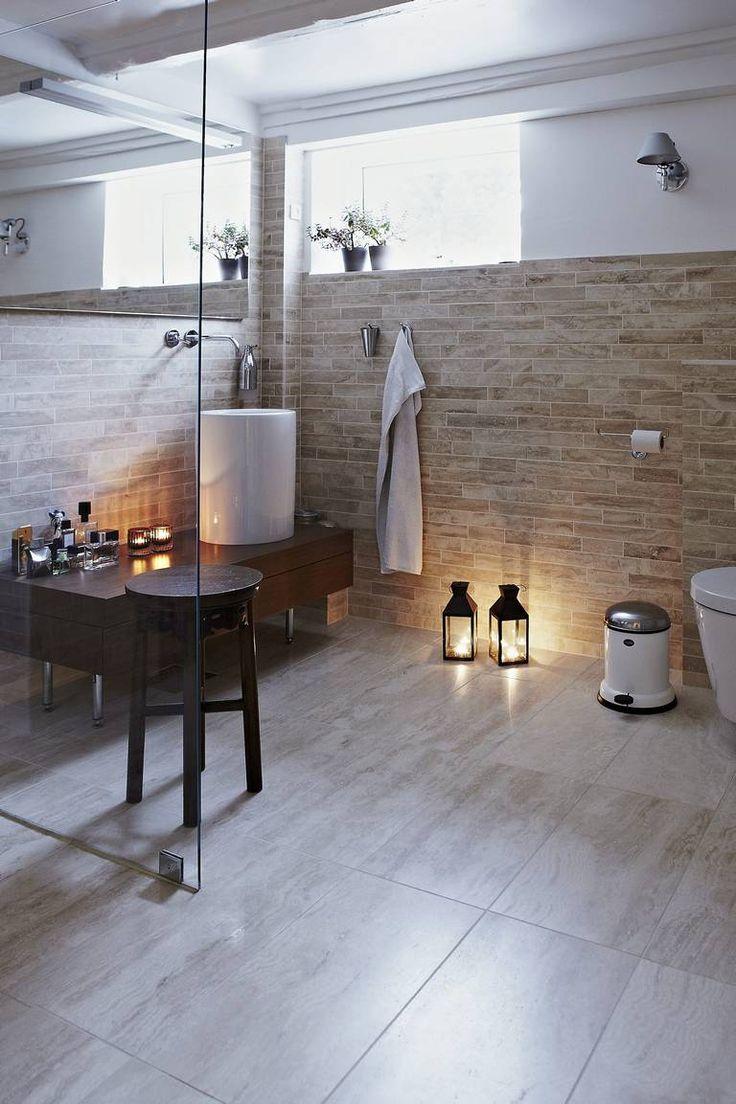 STEMNINGSFULLT. Også badet ligger i kjelleren.Det er holdt i gylne toner med italiensk travertinmarmorfra Banio. Store fliser på gulvet står i fonkontrast til de små på veggene. Blandebatteri,vask og toalett er designet av Philippe Starck.