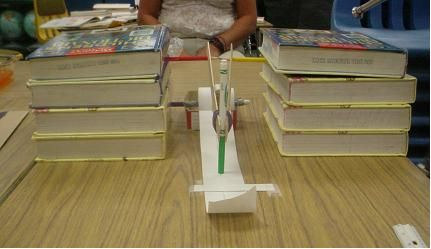 A photograph of an assembled, homemade seismograph constructed out of common classroom materials. There is a marker held by rulers that when hit, the marker will draw a line on a paper below.