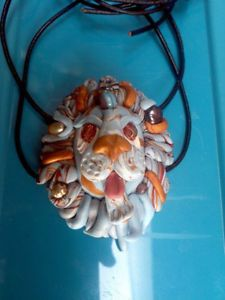 Lion necklace. Hand crafted lion head necklace strung on black leather cord with adjustable knots. He is made of polymer clay with Fresh water pearls, crystals and firepolished beads for accents.His eyes are copper firepolished faceted beads. He was made as a fundraiser for Queen Mary school that never took place. He would make an excellent pull for a zipper, a focal bead, or as he is - an adjustable lion. He has two holes through him and would work very well in macrame or beading.