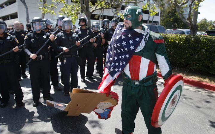 """Erik Lopez of Hercules dressed as """"Captain Mexico"""" joins protesters gathered outside the Hyatt Regency Hotel where Republican Presidential candidate Donald Trump kicked off the California Republican Party Convention in Burlingame."""