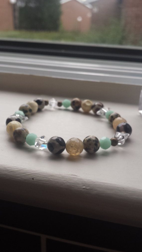 https://www.etsy.com/listing/200169105/multi-tone-beaded-bangle?ref=related-2    * Silver Tone hammered Bead 10 mm  * Silver Tone round donut spacers 6mm  * Mint Alabaster Swarovski Round 6mm and 8mm  * Jasper bead Bone and Bone and Brown 8mm  * on stretch cord