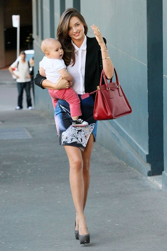 Not only rocking a mini and pumps, but also carrying a baby...now that is talent