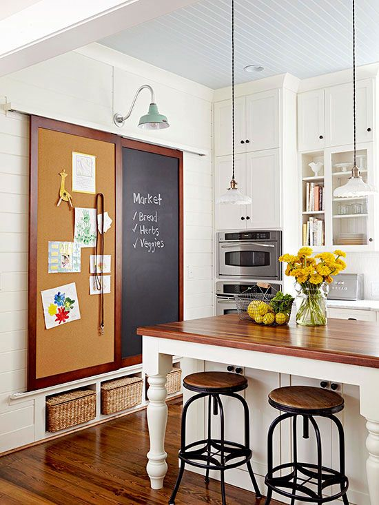 Savvy Storage Sliding message boards conceal a recessed pantry just shallow enough to minimize rummaging but deep enough for small appliances. Hung from double-track barn-style hardware, the cork and chalkboard doors minimize clutter in the heavy-foot-traffic area. A pastel light fixture provides a vintage pop of color above.