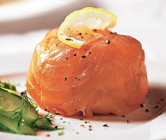 Smoked salmon parcel with slice of lemon on top, served with cucumber slices