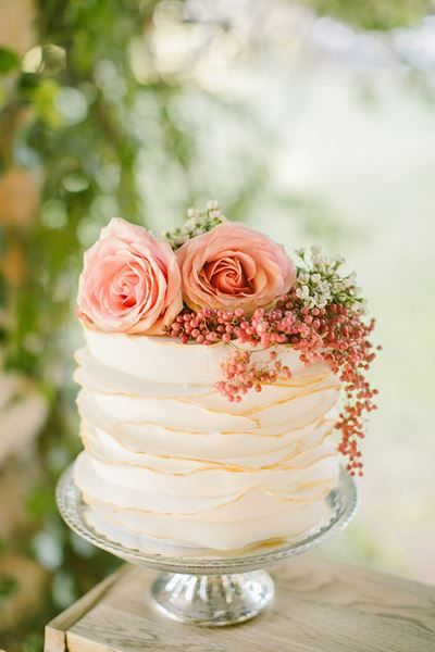 Ruffled buttercream cake with pink roses on top.