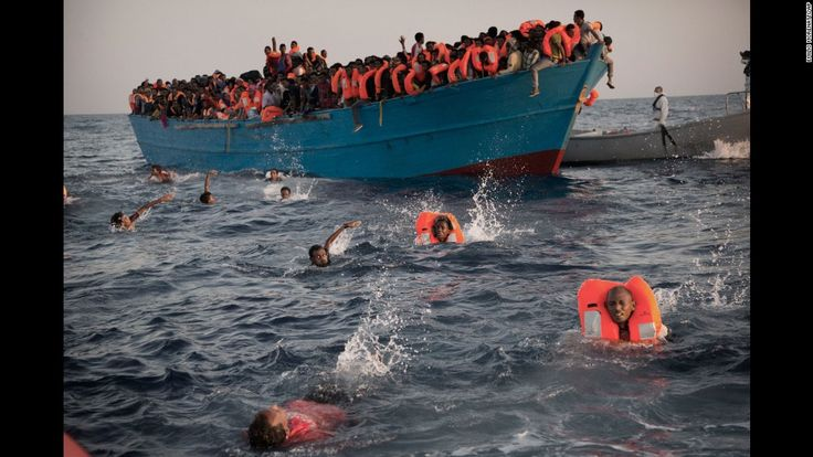 Migrants, most of them from Eritrea, jump into the Mediterranean from a crowded wooden boat during a rescue operation about 13 miles north of Sabratha, Libya, on Monday, August 29.