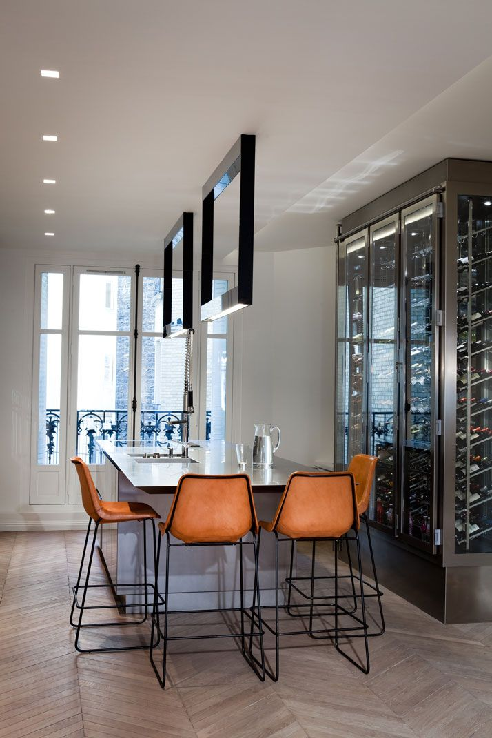 Pub height table, chairs in orange, and frame room dividers at the ceiling! Elegant. (Apartment Near The Eiffel Tower)