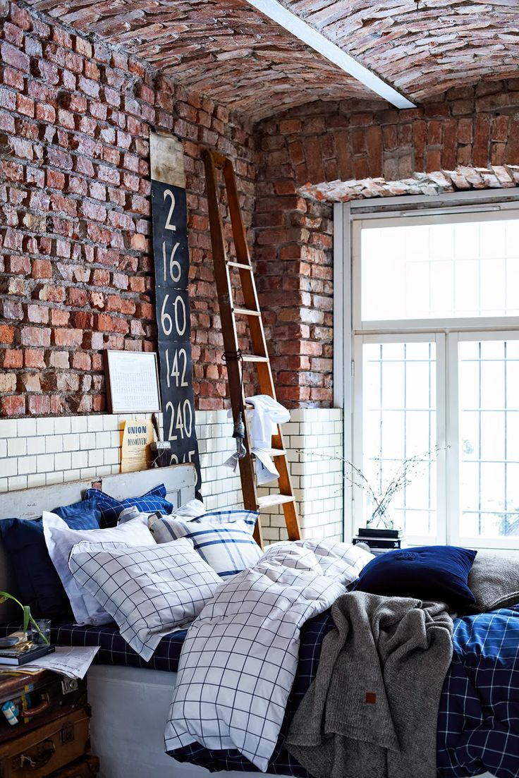 Blue & white bedding looks kind of fresh. And those brick walls and windows are just lovely!
