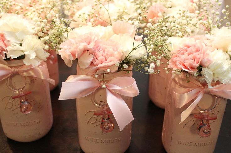 Baby shower centerpieces. I painted each jar pink, lightly sanded it to give it that rustic look. Added a ribbon with decor pacifier and finished it off with pink and white carnations and babies breath. Simply beautiful!