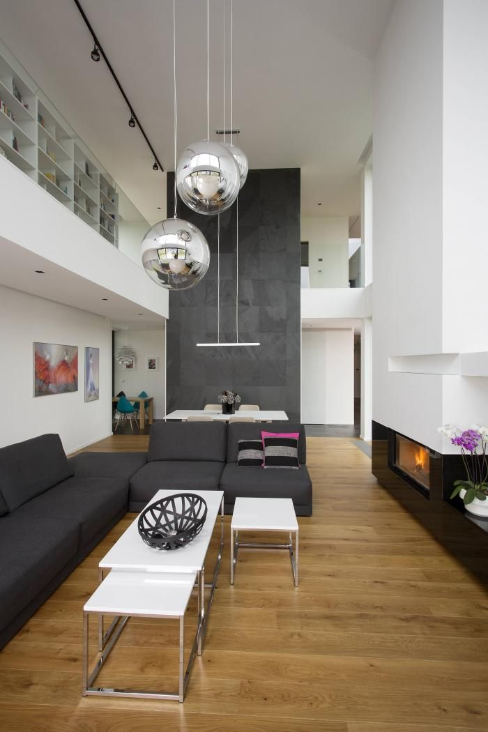 Unique, modern architecture with high ceiling.    #house #livingroom #mirrorballlamp #tomdixon #comforty #sofa #fireplace #highceiling #modern