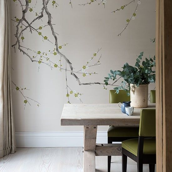 Neutral dining room with feature wall A feature wall with hand-painted wallpaper is the focal point of this beautiful modern dining room. Keep curtains and flooring plain and neutral so that the wallpaper takes centre stage and pick up echoes of the leaf design with the real thing, potted up and lovely in a feature container. Here green chairs further emphasise the accent colour.