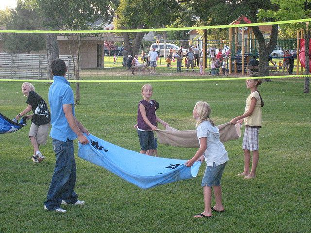 WATER BALLOON VOLLEYBALL-Throw and catch water balloons over a volley ball net using a beach towel.