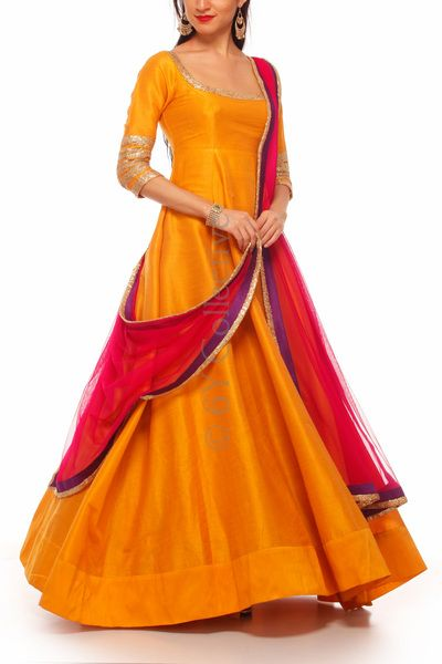 Imbued with a gleaming goldenrod hue this mustard gold anarkali highlights curves before flaring into a stunning skirt.    Description Mustard Floor-length Anarkali with Sequin striped sleeves Stylized sequin scoop neckline with deep scoop back with tie-back strings; Built-in cups at bodice for perfect form fit    Includes Rani net dupatta with purple Benaras Rawsilk panels on all sides paired with sequin trimming Does not require leggings    Construction Details 3/4th sleeve with sequin...