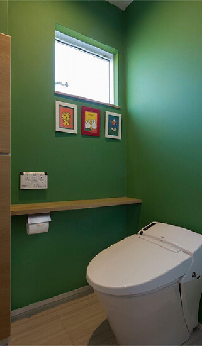トイレ お気に入りの絵本をイメージした鮮やかなグリーンの壁紙で