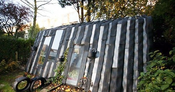 Second-hand tires and windows are re-used in this backyard structure that stores stuff and doubles as an office shed for an expanding family.