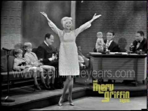 "Less than a year before her tragic death, Jayne Mansfield visits Merv and Henny Youngman with four dogs and four kids in tow, including an adorably precocious 2-year-old Mariska Margitay, star of Law & Order: SVU. Fun and frolic ensue and then Jayne wows them with a campy version of ""Diamonds Are A Girl's Best Friend."" Merv Griffin had over 5000..."