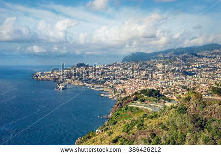 Tropical city of Funchal, Madeira, Portugal with blue ocean, few clouds and major cruise ship.