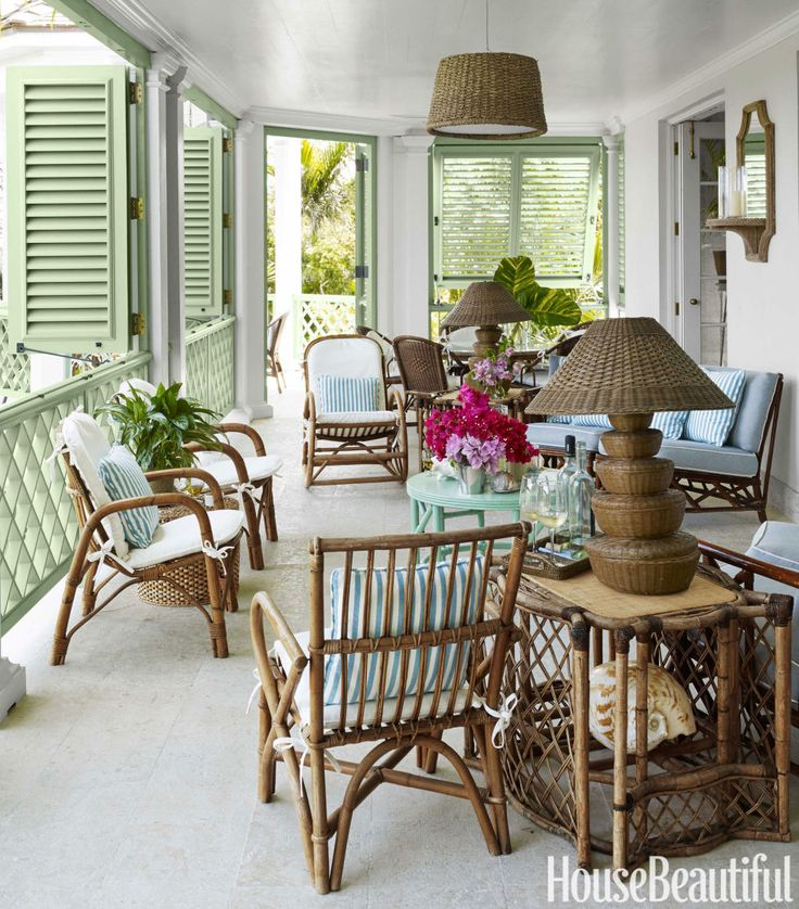 Rattan furniture creates a relaxed living room on the veranda. Shutters and railings are painted Southfield Green by Benjamin Moore in Aura Exterior. Lamps, Circa Who.