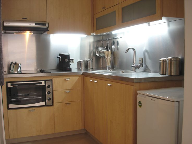stainless steel makes a great contrast with the light wood of the cabinets.