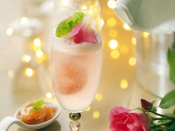 Cocktail van champagne en rosé met rozenblaadjes en munt