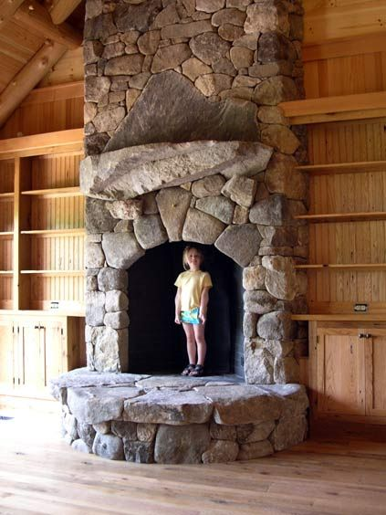 Arched opening fieldstone fireplace with keystone, natural stone mantel with unique mountain shaped stone backing